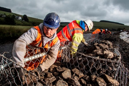WORKERS FILLING GABIONS